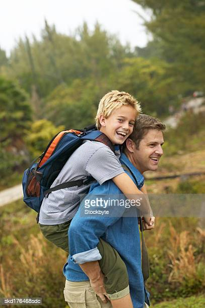 father giving his son (10-11) a piggyback
