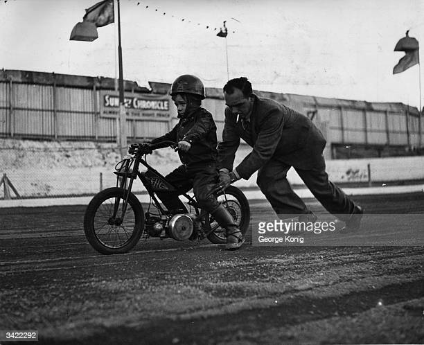 A father giving his son's motorbike a push start at the Cradley Heath track in Wolverhampton