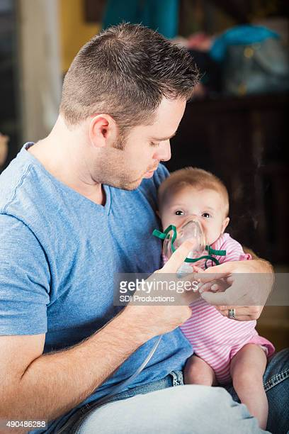 Father giving infant daughter breathing treatment for cystic fibrosis