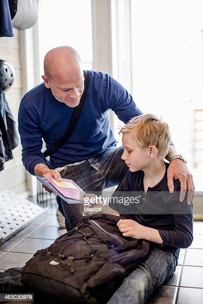 Father giving notebook to son sitting on floor at home