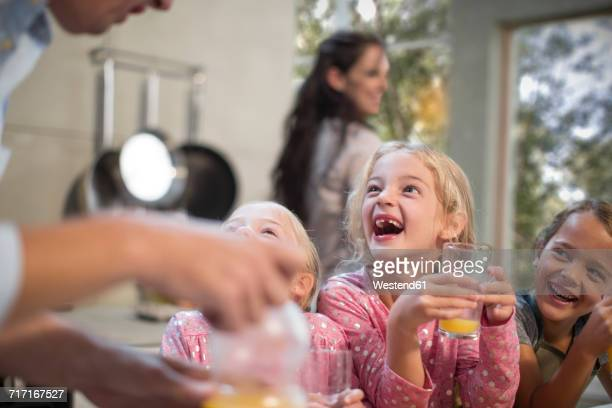 Father giving orange juice to happy girls at home