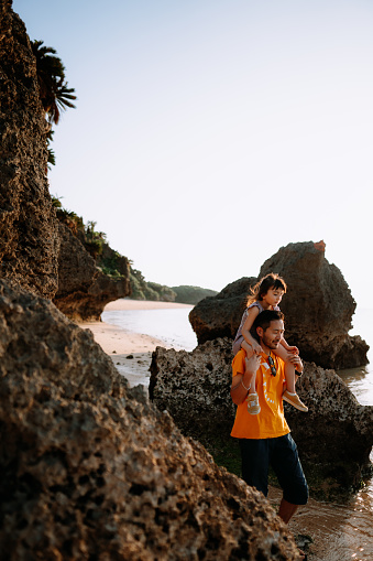 Father giving preschool daughter piggyback ride on beach at sunset, Ishigaki Island, Japan - gettyimageskorea