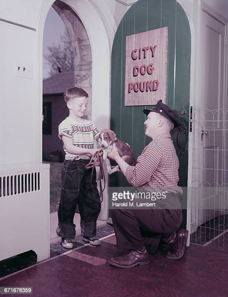 father giving puppy to son at door  - pawed mammal stock pictures, royalty-free photos & images