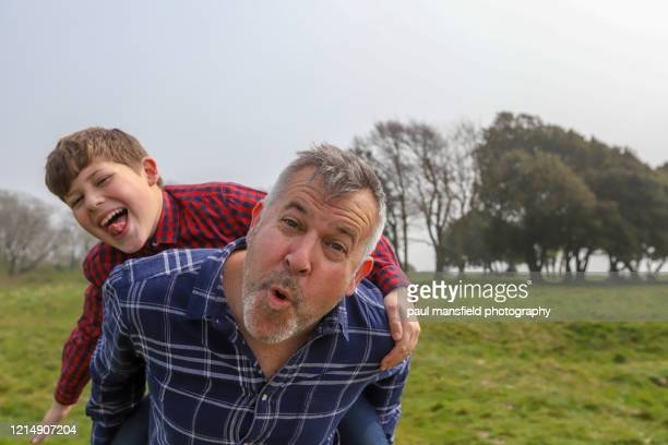 father giving son a piggyback - piggyback stock pictures, royalty-free photos & images