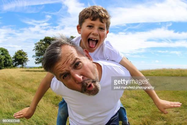 father giving son a piggyback - piggyback stock photos and pictures