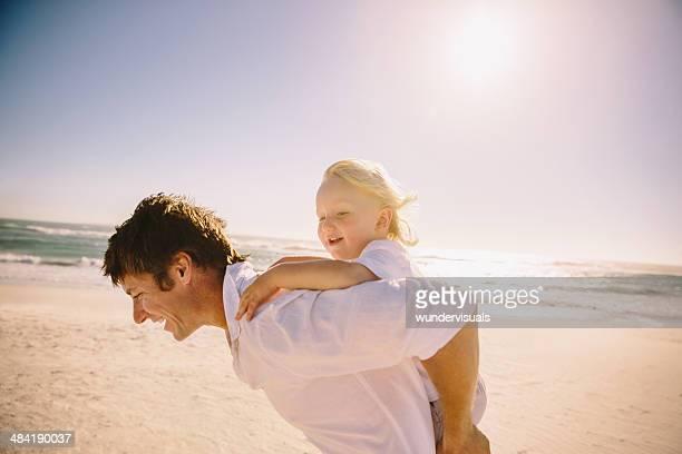 Father giving son a piggyback ride on beach
