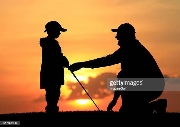 Father Giving Son Junior Golf Lesson