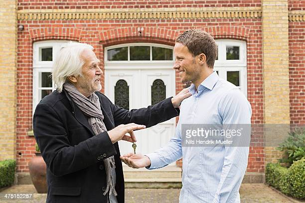 Father giving son key outside house