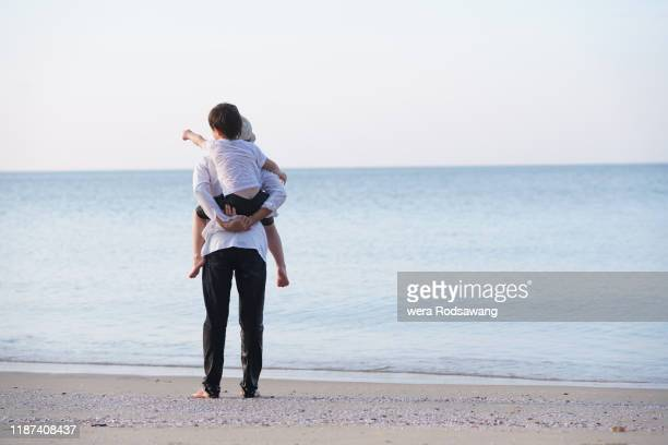 father giving son piggyback ride during walking along the beach - piggyback stock pictures, royalty-free photos & images