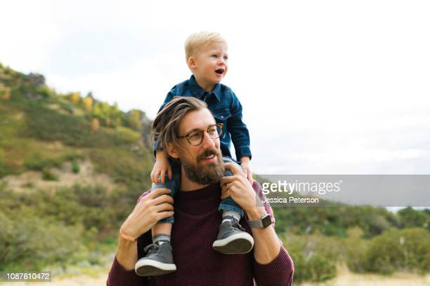 father giving son piggyback ride - carrying on shoulders stock pictures, royalty-free photos & images