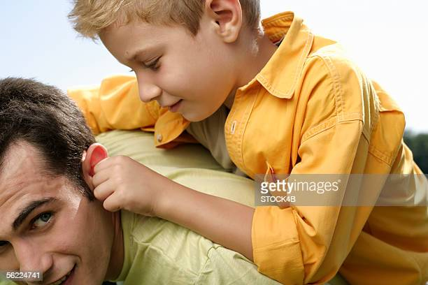 Father giving son piggyback ride, while son pulls at father's ear