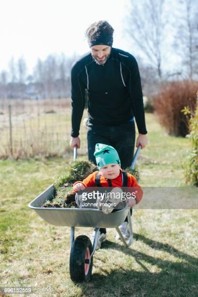father giving son ride in wheelbarrow - printemps humour photos et images de collection