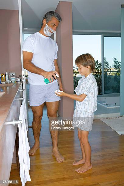 father giving son shaving foam. - boxershort stock pictures, royalty-free photos & images
