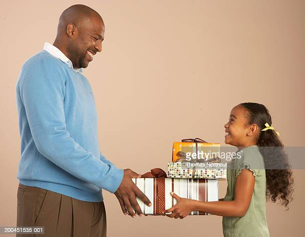 Father giving stack of gifts to daughter (8-10), smiling, side view