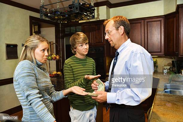 Father giving teenage son and daughter money