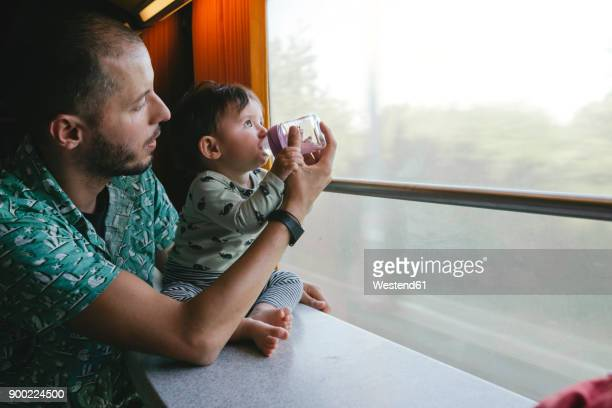 Father giving water to his baby girl in a baby bottle while traveling by train