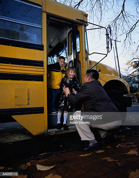 Father Greeting Daughter at a School Bus