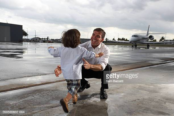 Father greeting son (3-5) on airport runway, smiling