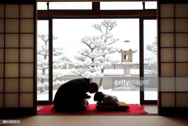 Father greeting with baby in background of snowy garden