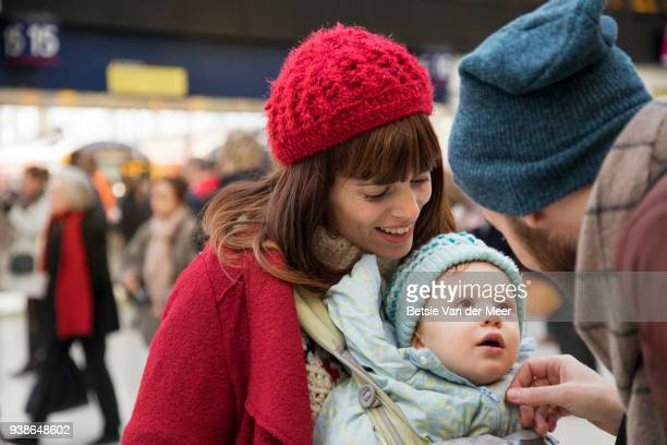 father greets baby son and mother at arrival hall. - toddler at airport stock pictures, royalty-free photos & images