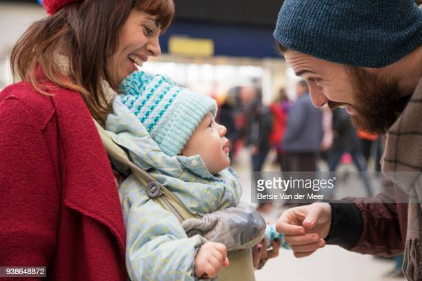 Father greets baby son and mother at arrival hall.