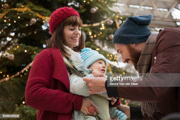 Father greets child and mother in arrival hall near christmas tree.