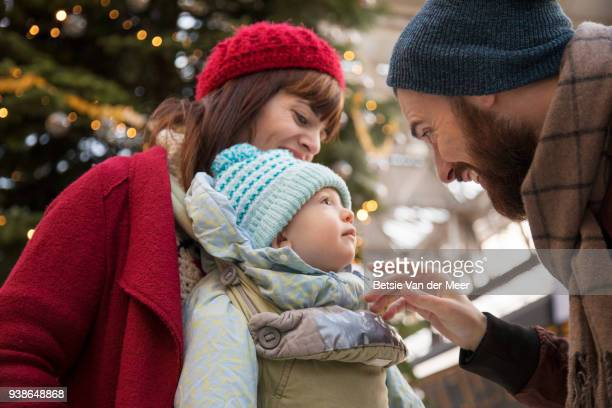 Father greets mother and child waiting in arrival hal near christmas tree.