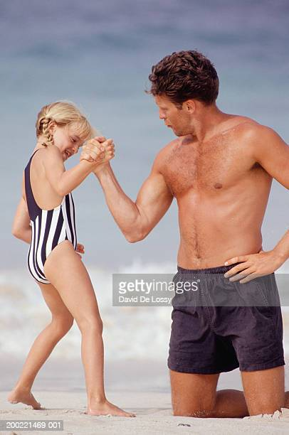Father hand wrestling with daughter (6-7) on beach
