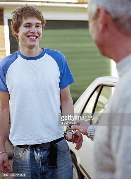 Father handing adult son car keys