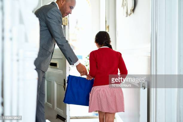 father handing school bag to daughter leaving through front door - girls stock pictures, royalty-free photos & images