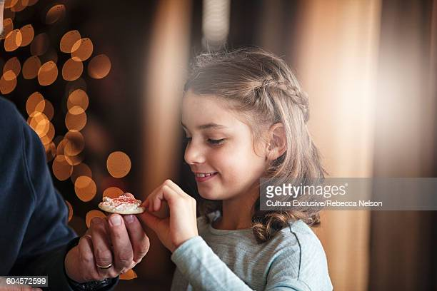 Father handing smiling daughter christmas cookie