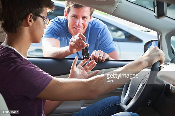 Father handing son car keys