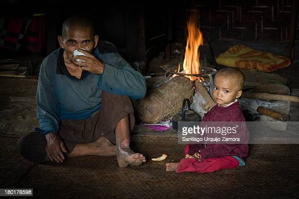 Father having a cup of tea and relaxing with his son by the fireplace of his house. They belong to the Palaung tribe, a Mon-Khmer ethnic minority...