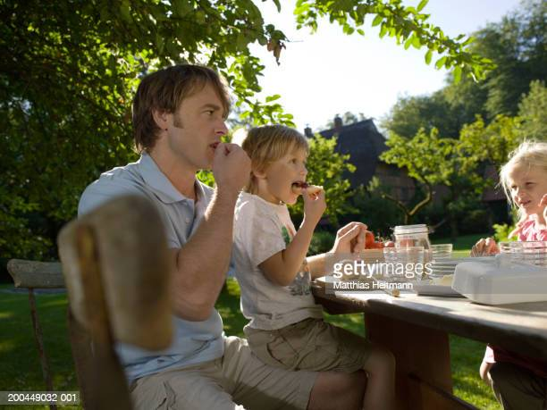 Father having breakfast in garden with son and daughter (3-5)