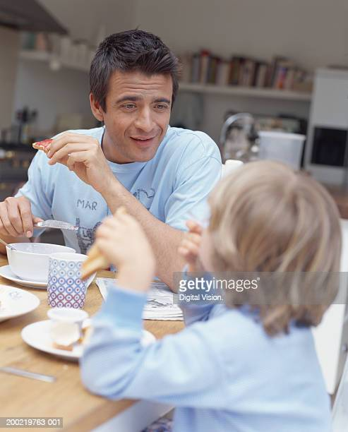 Father having breakfast with son (4-6) smiling