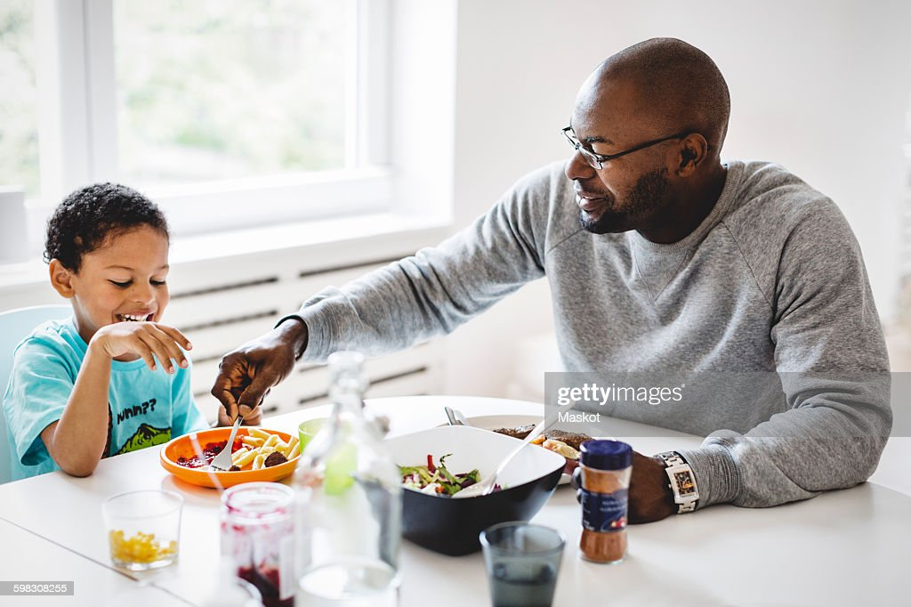 Father having food with son at dining table in house : Stock Photo
