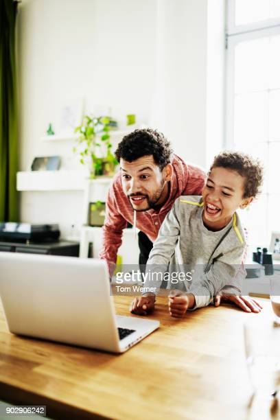 father having fun with son playing on computer together - homme maghrebin photos et images de collection