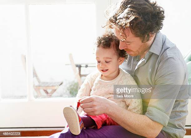 father helping child put on shoes
