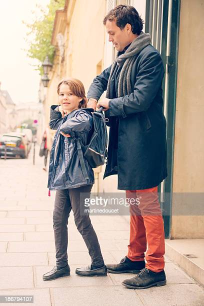 Father helping child to put on backpack in european street.