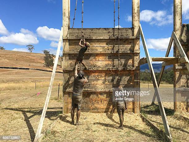 Father helping children complete mud run obstacle
