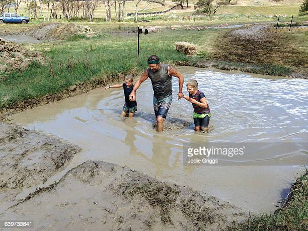 Father helping children through mud run obstacle