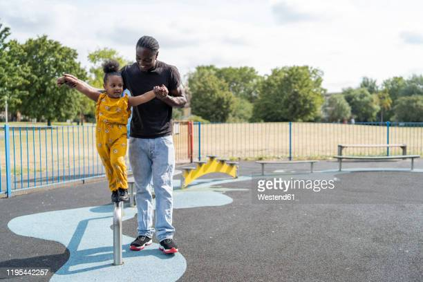 father helping daughter balancing on a bar on a playground - britain playgrounds stock pictures, royalty-free photos & images