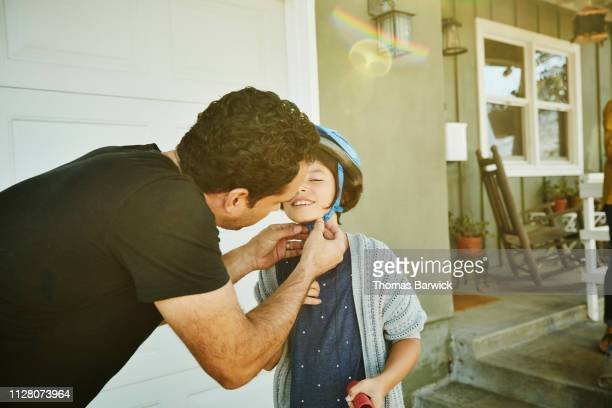father helping daughter buckle helmet before riding scooter - responsabilidade - fotografias e filmes do acervo