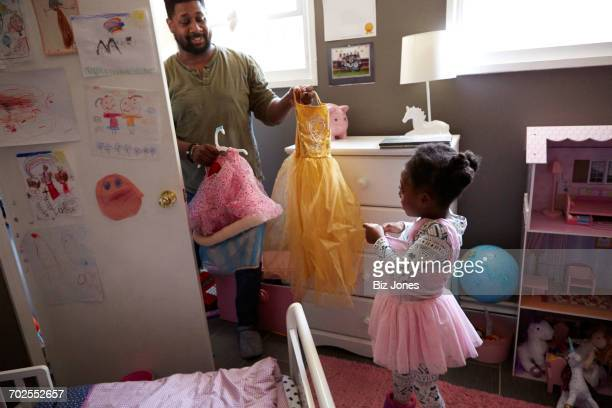 Father helping daughter choose party outfit