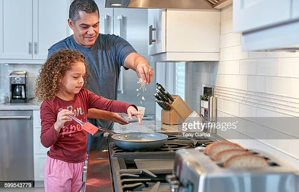 Father helping daughter cook on hob in kitchen, sprinkling cheese