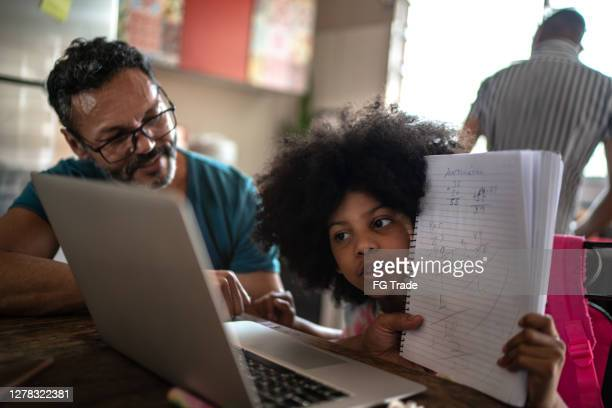 father helping daughter during videochat/homeschooling at home - remote location stock pictures, royalty-free photos & images