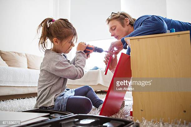 father helping daughter in making toy kitchen - diy stock pictures, royalty-free photos & images