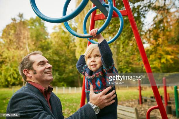 father helping daughter on monkey bars in playground - britain playgrounds stock pictures, royalty-free photos & images