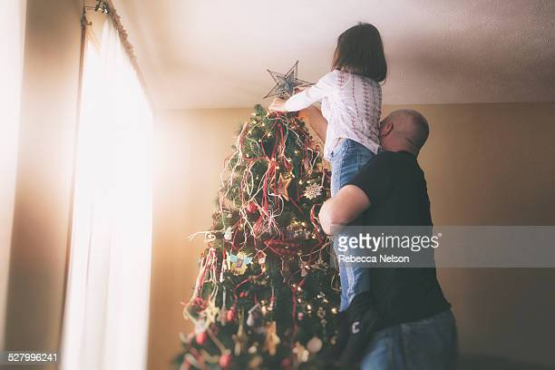father helping daughter put star on Christmas tree