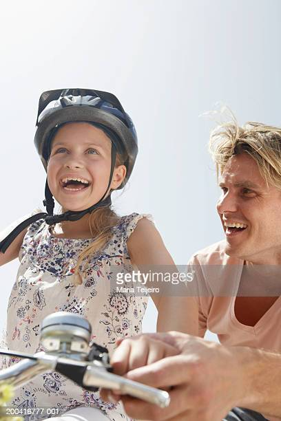 Father helping daughter (9-11) ride bicycle, low angle view